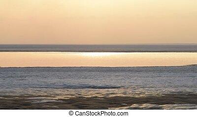 Spring landscape on the sea. Snow melting. Sunset.