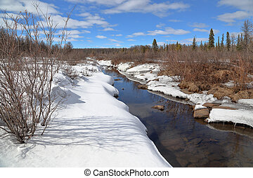 Spring landscape with a melted stream in South Yakutia, Russia
