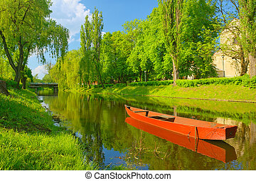 Spring landscape with boat on the river.