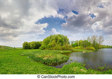 Spring landscape with lake, meadow, forest and sky with clouds