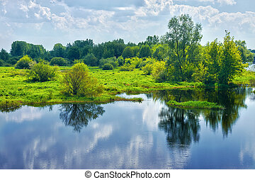 Spring landscape with river and clouds on the sky