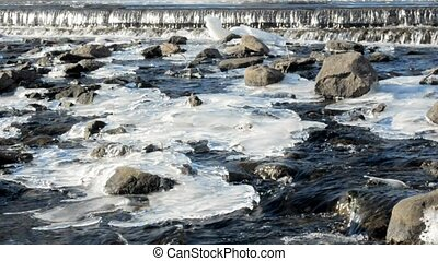 River rapids with rocks and icy patches - Spring melting of...