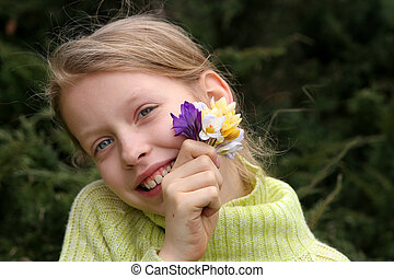Spring mood - Young smiling girl with a bunch of crocuses