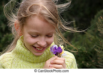 Young, laughing girl with a bunch of crocuses