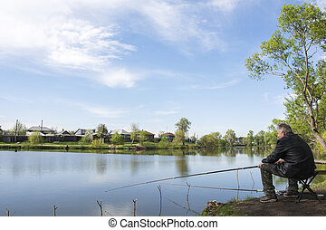 Spring on the lake fisherman sitting on a wooden pier.
