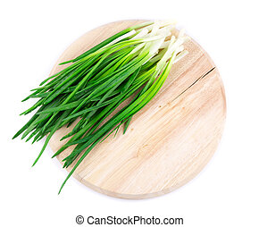 Spring onions on the wooden cutting board.