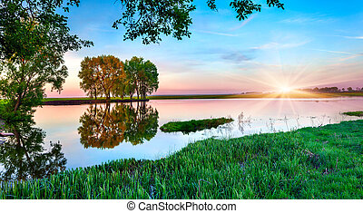 Spring panorama of morning with rising sun on lake
