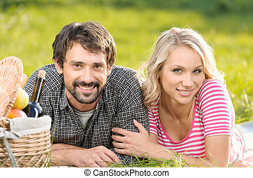 Spring picnic. Loving young couple enjoying a romantic picnic in park together