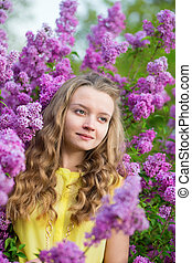 Spring portrait of a beautiful girl with lilac