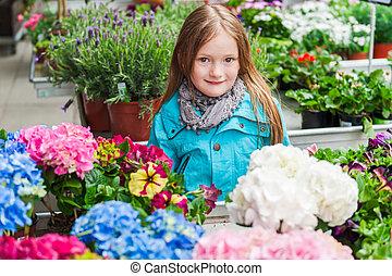 Spring portrait of a cute little girl choosing flowers in flower shop