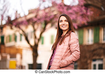 Spring portrait of pretty young woman posing outdoor