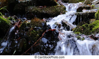 Spring river flowing between the mossy rocks, close up