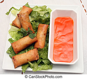 Spring roll plate - A plate of spring rolls on a bed of...