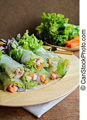 spring rolls with fresh vegetable on wooden table