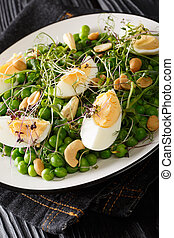 Spring salad of green peas, micro green, nuts and cooked eggs close-up on a plate. vertical