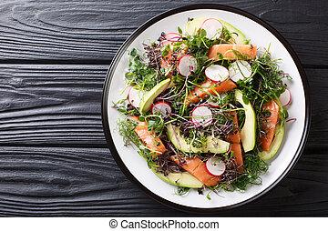 Spring salad of salmon, avocado, radish and mix microgreen close-up on a plate. horizontal top view