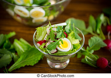 spring salad with arugula, boiled eggs, fresh radish, salad leaves in a glass bowl