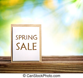Spring Sale sign on rustic wooden board over shiny green background