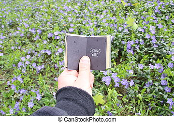 spring sale text and field with blue flowers
