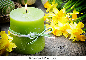 Spring setting with yellow narcissus and candle