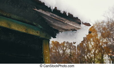 Spring Snow Melting on the Roof Old House