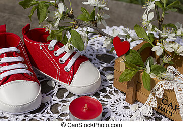 Spring still life with red children's bootees