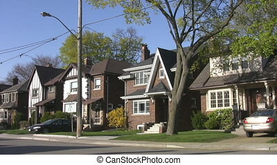Spring street scene with big green tree. Houses in the suburb of East York, Toronto, Ontario, Canada.