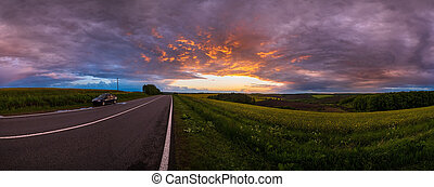 Spring sunset rapeseed yellow blooming fields and road