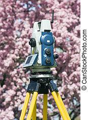 Spring surveying - theodolite against blosoming tree.
