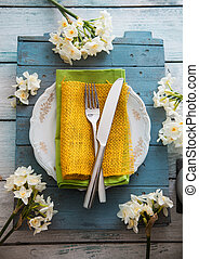 Spring table setting. Narcissus flower. Fork and knife on...