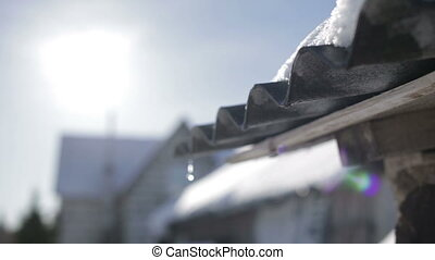 Spring thaw - Melting snow on the roof on a sunny spring day