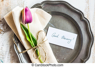 Spring time table setting with tulip flowers and good...