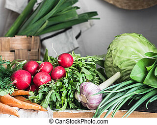 Spring vegetarian food ingredient variety. Assortment of spring vegetables for healthy cooking over rustic cupboard, white wall background. Healthy vegetarian vegan food from the local market