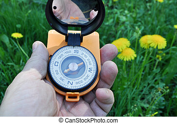 Compass in hand, against the background of blooming meadows.