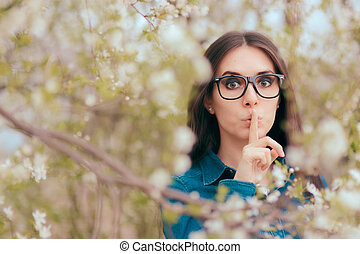 Spring Woman Wearing Eyeglasses Keeping a Secret in Blooming Nature