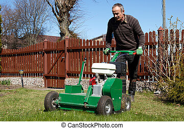 Man working with Lawn Aerator - Spring work in garden. Man...