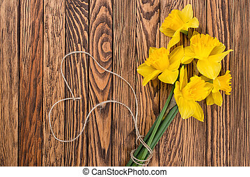 Spring yellow  daffodils  flowers and empty tag on brown painted wooden planks. Selective focus. Place for text.
