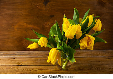 Spring yellow tulips bouquet on wooden background