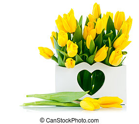 spring yellow tulips in wooden basket isolated on black...