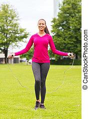 springt-touw, glimlachende vrouw, het uitoefenen, buitenshuis