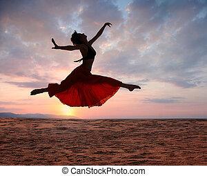 springt, vrouw, op, ondergaande zon