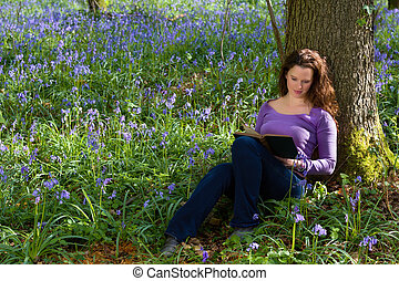 Springtime bluebells and a book - Attractive young woman...