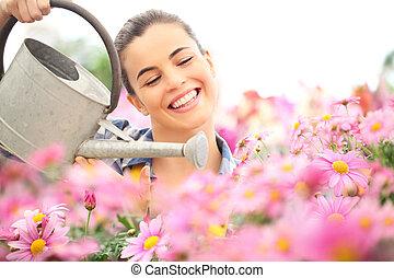 springtime, smiling woman in garden watering daisies flowers