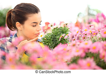 springtime woman smells the daisies in flowers garden