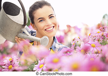 springtime woman smiling in garden of daisies flowers with watering can