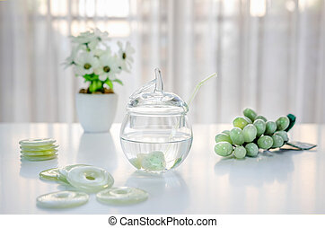 Springwater in a glass jar is charged with the healing energy of jade stones