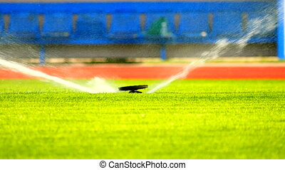 Sprinkler Watering a Sports Field. Working sprinklers with strong water spray