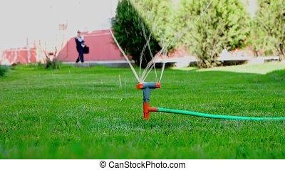 Sprinkler working and woman walking on background in slomo...