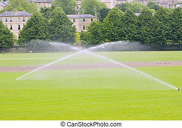 Sprinklers - Two sprinklers irrigating a sports field in...