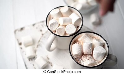 Sprinkling chocolate on marshmallows in mug with cocoa, top view